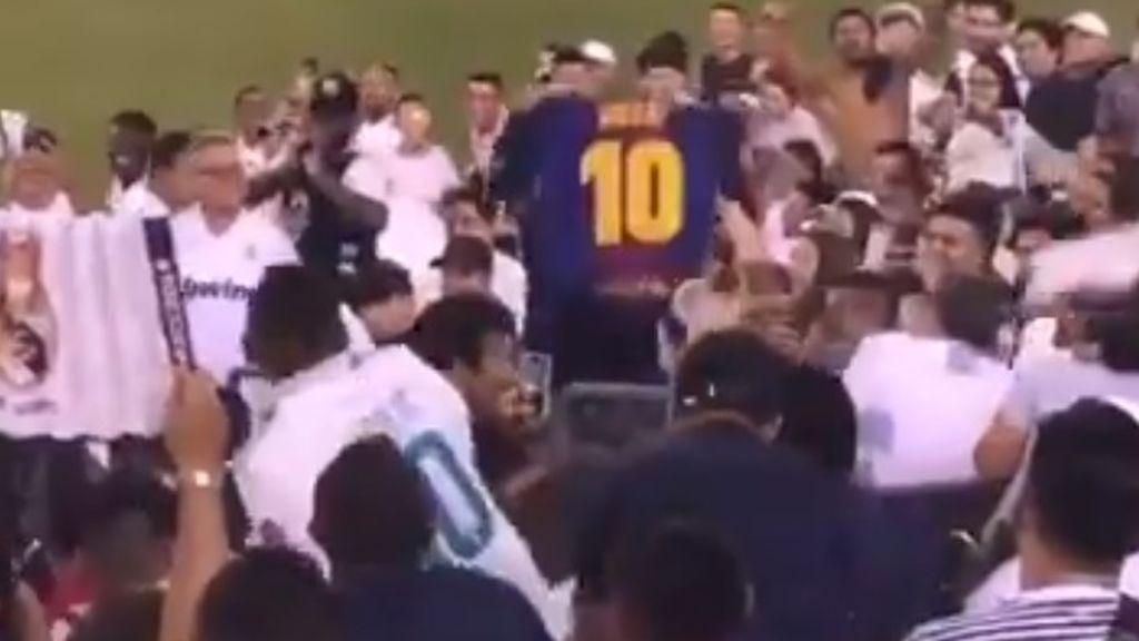 Un aficionado del Barça recibe una lluvia de objetos tras mostrar una camiseta de Messi en el derbi entre Real Madrid y Atlético