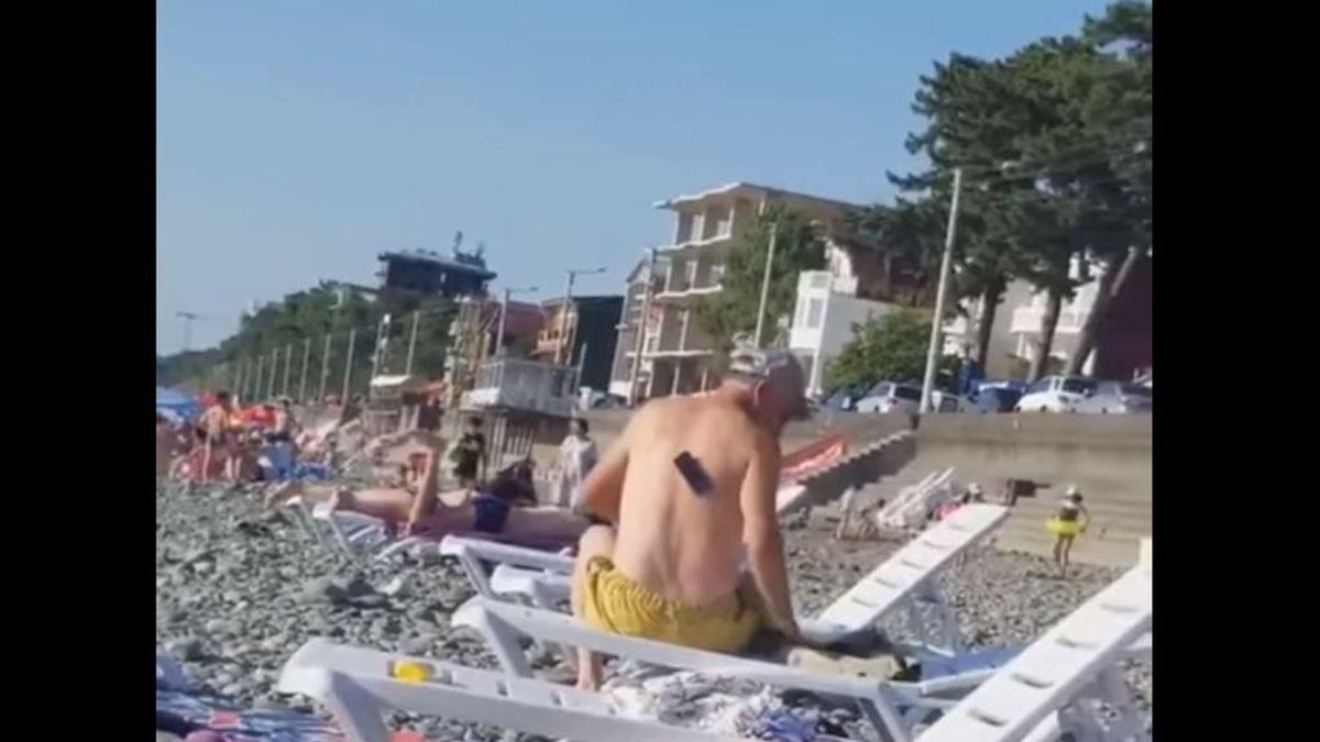 Los problemas veraniegos del móvil y la playa: un hombre busca desesperado su teléfono sin saber que lo tiene en su espalda