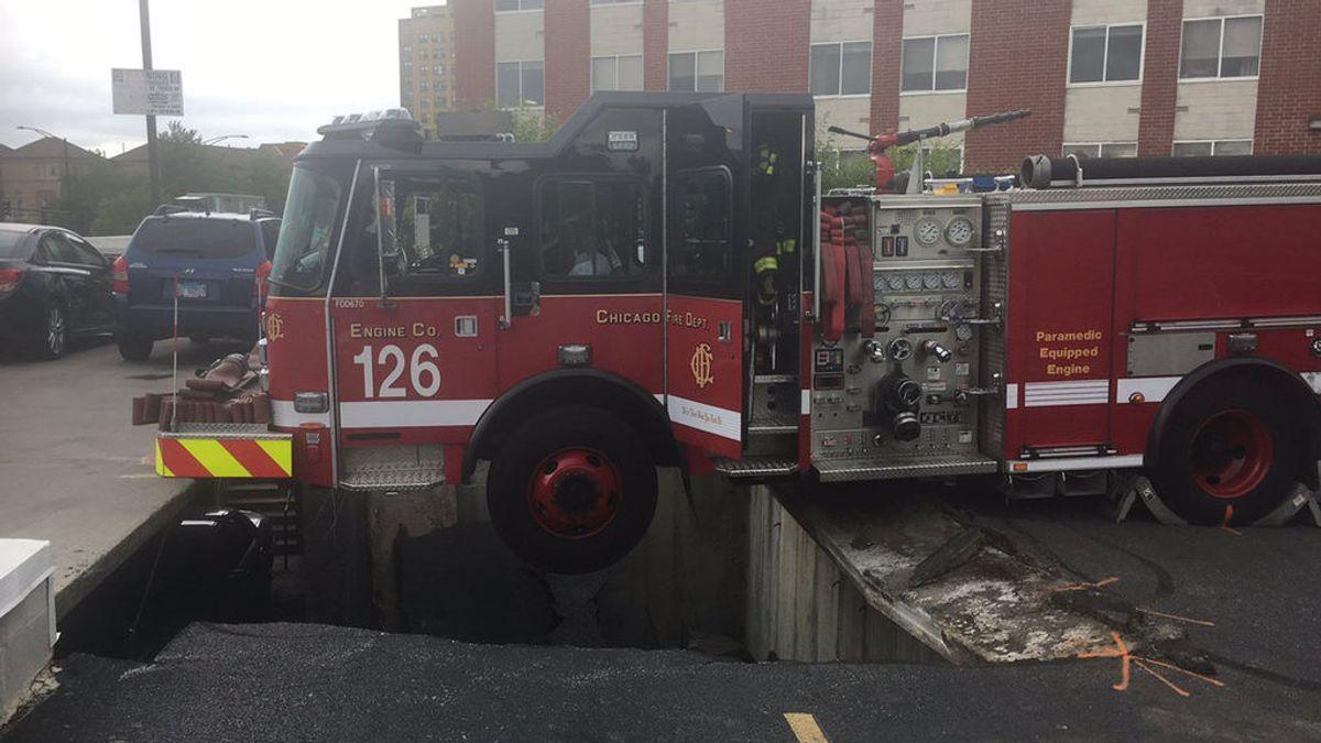 Un camión de bomberos, a punto de caer por un socavón tras derrumbarse la calzada por la que circulaba