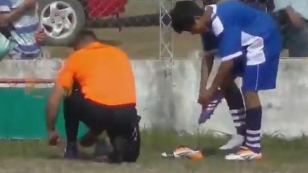 Un árbitro le da sus botas a un jugador para que pueda seguir jugando después de que se le rompieran