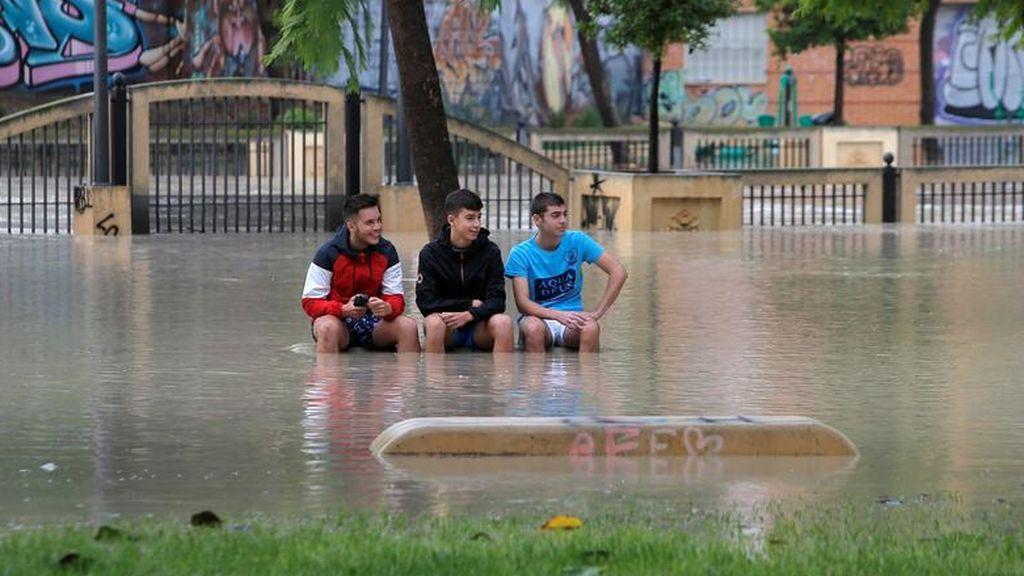 Niños se sientan en un banco en un parque cerca del desbordante río Segura mientras las lluvias torrenciales azotan Orihuela
