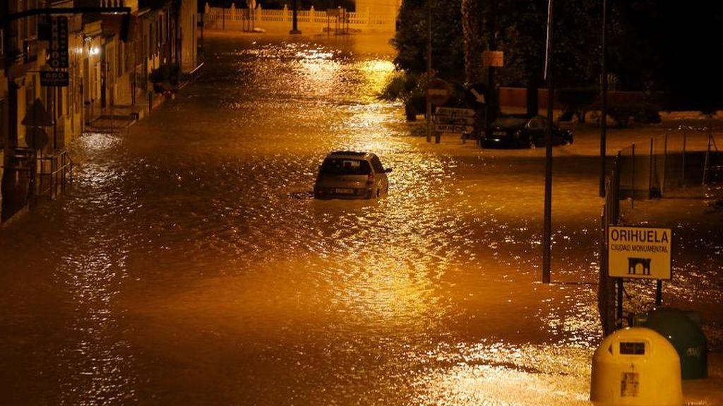Un automóvil atascado en una calle inundada cuando las lluvias torrenciales azotan Orihuela
