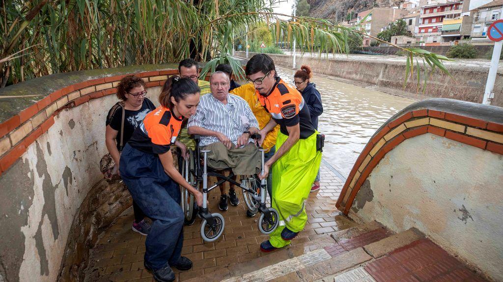 Voluntarios de protección civil trasladan a un hombre en silla de ruedas tras las intensas lluvias esta tarde en Murcia