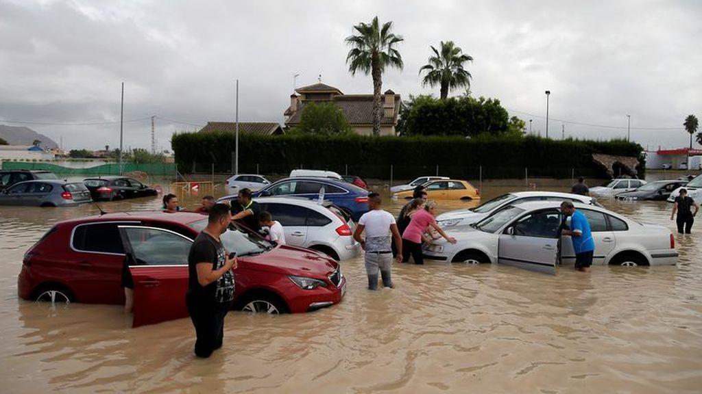 Vecinos cerca de los coches inundados en Orihuela