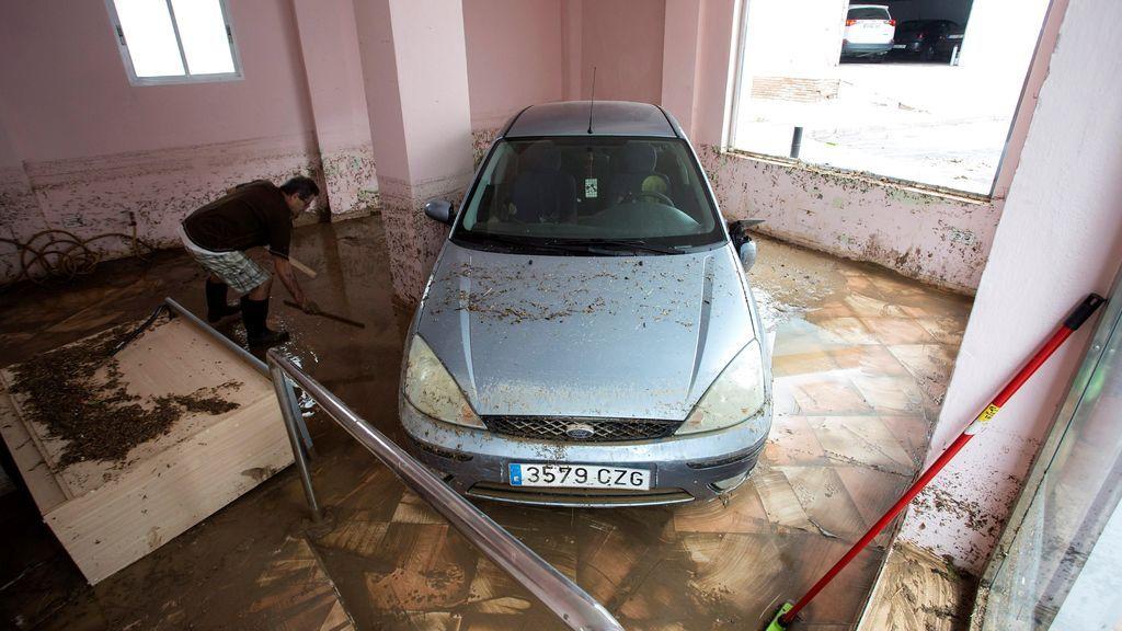 Una persona realiza tareas de limpieza en un local hasta donde ha sido arrastrado un vehículo en Málaga