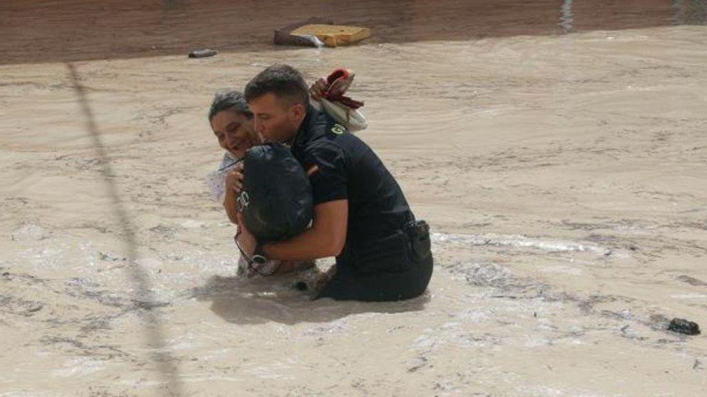 un guardia civil rescatando a una mujer en medio de las riadas