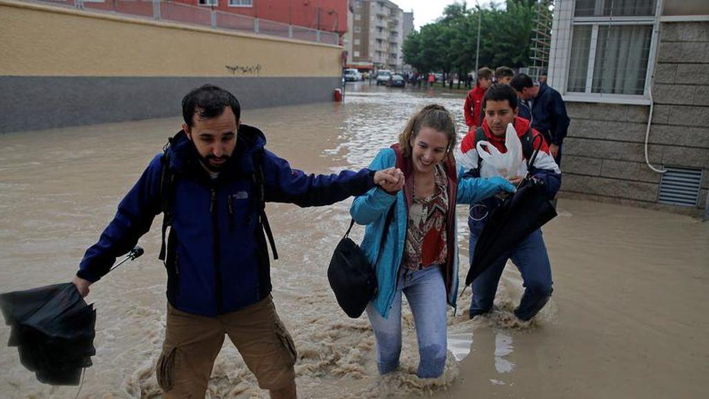 La gente camina por una calle inundada cerca del desbordante río Segura