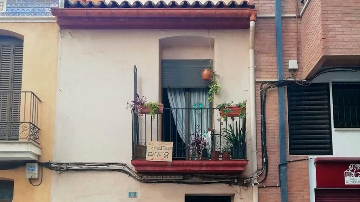 """""""El prostíbulo en el número 8"""", este cartel, en su balcón, resume la vida imposible que vive un matrimonio, en Castellón."""
