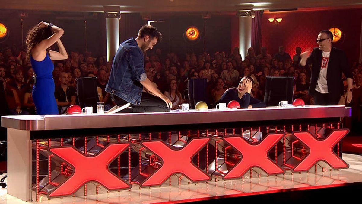 Dani intenta proteger con su cuerpo el botón rojo para no pausar la actuación de su pueblo y acaba dándole sin querer