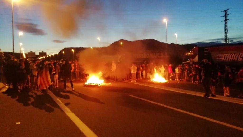 Manifestantes quemando palets en al C17