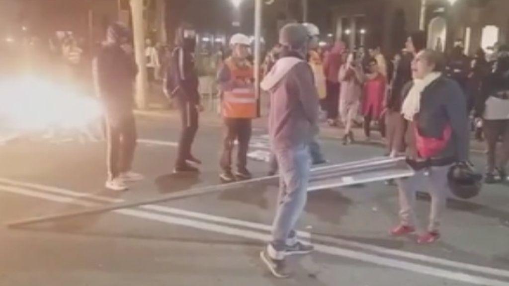 Una señora impide que un manifestante arroje una señal de tráfico a una barricada en Barcelona