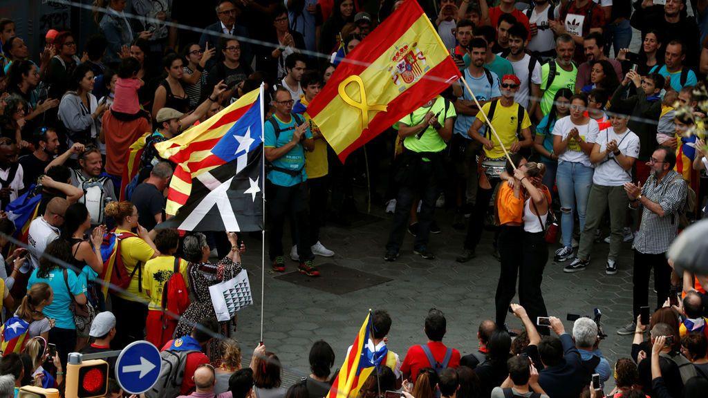 Manifestantes independentistas aplauden a dos jóvenes con una bandera de españa y un lazo amarillo