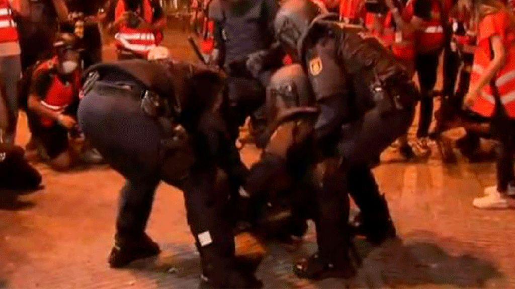 Un policía herido, socorrido por tres compañeros durante los disturbios en Barcelona