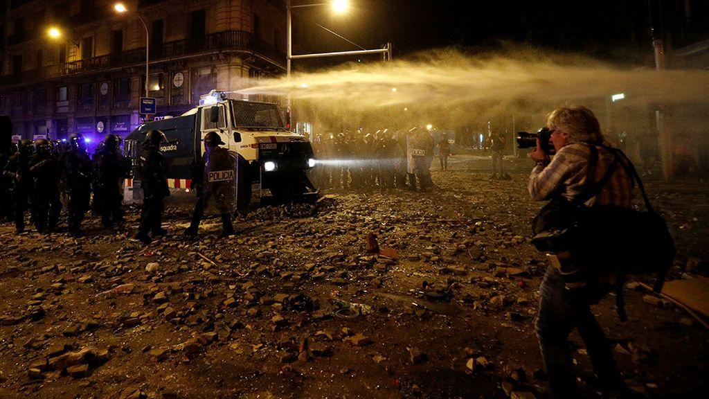 Agentes de los Mossos d'Esquadra utilizan un cañón de agua para tirar abajo las barricadas