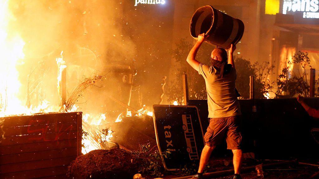 6.Un manifestante a punto de lanzar un contenedor al fuego de una de las barricadas