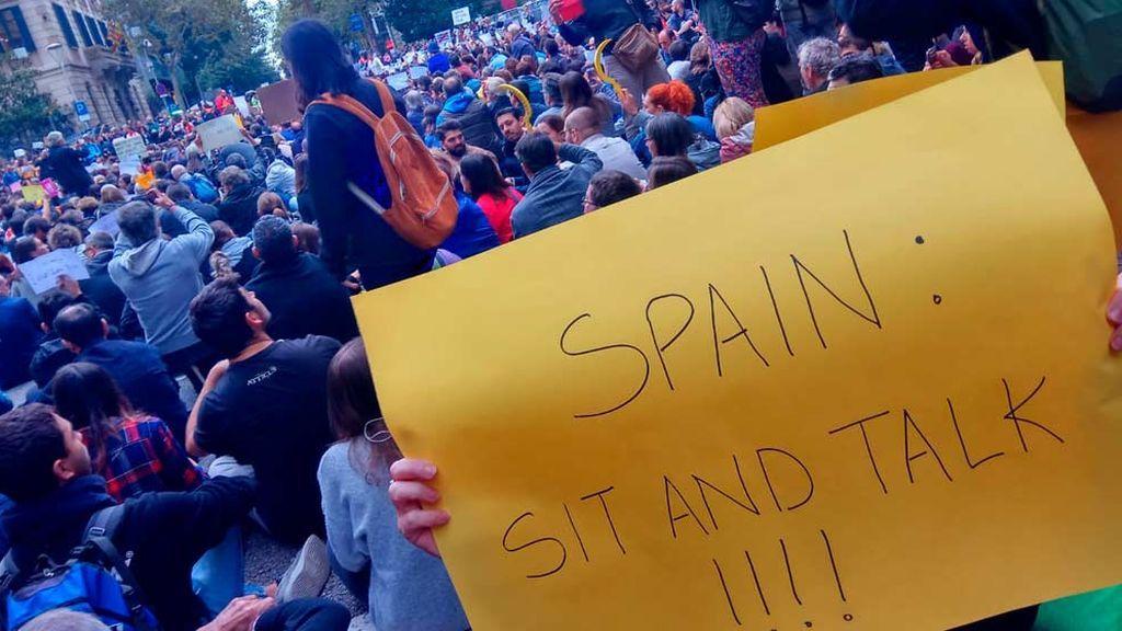 """Manifestantes con un cartel en el que dice: """"España: siéntate y habla"""""""