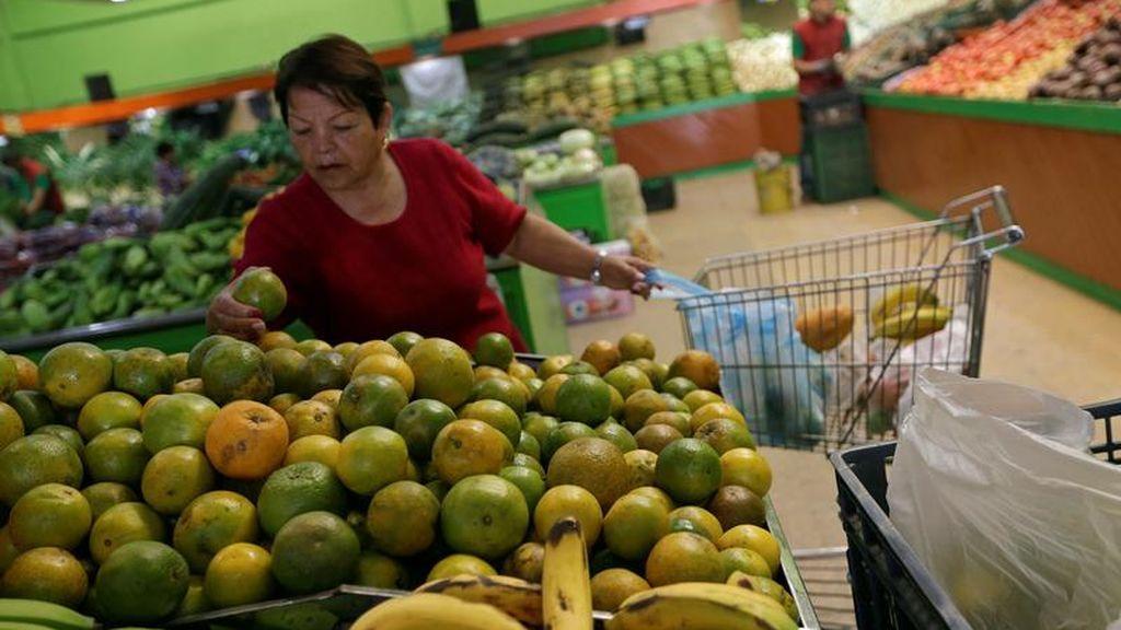 Una clienta compra fruta en un supermercado