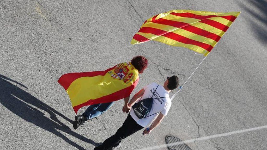 Una pareja porta las banderas de España y Cataluña
