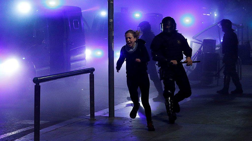 Una manifestante proindependencia huye de los antidisturbios