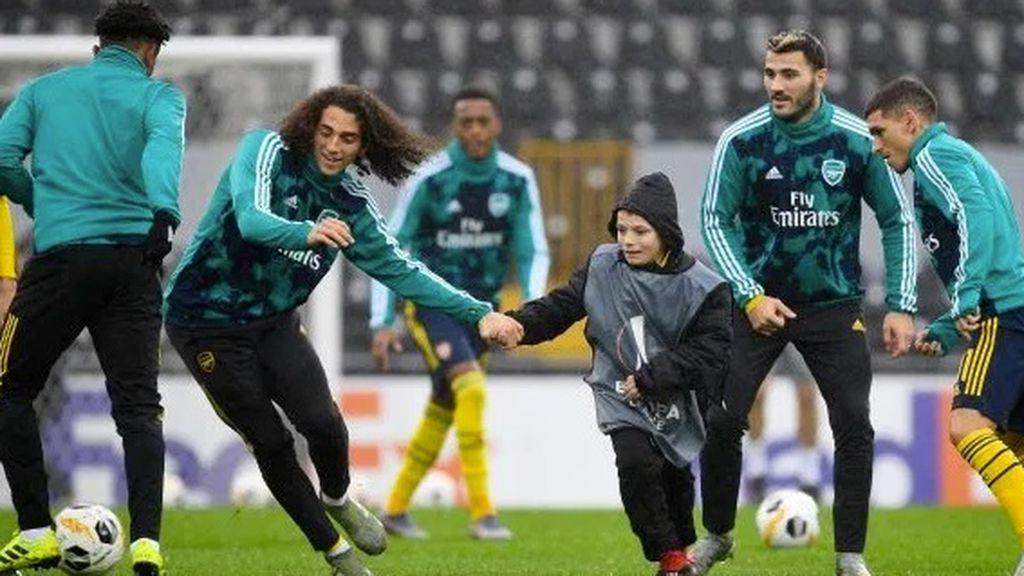 Un joven recogepelotas se une al entrenamiento del Arsenal antes de su partido en la Europa League