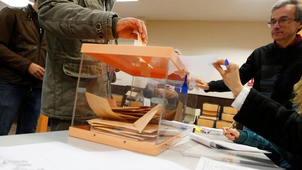 Varias personas votan en un colegio electoral de Madrid