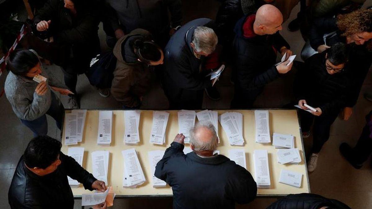 Varias personas eligen papeleta en un centro electoral de Madrid