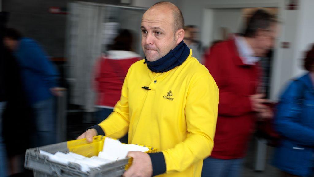Un empleado de Correos transporta los votos por correo