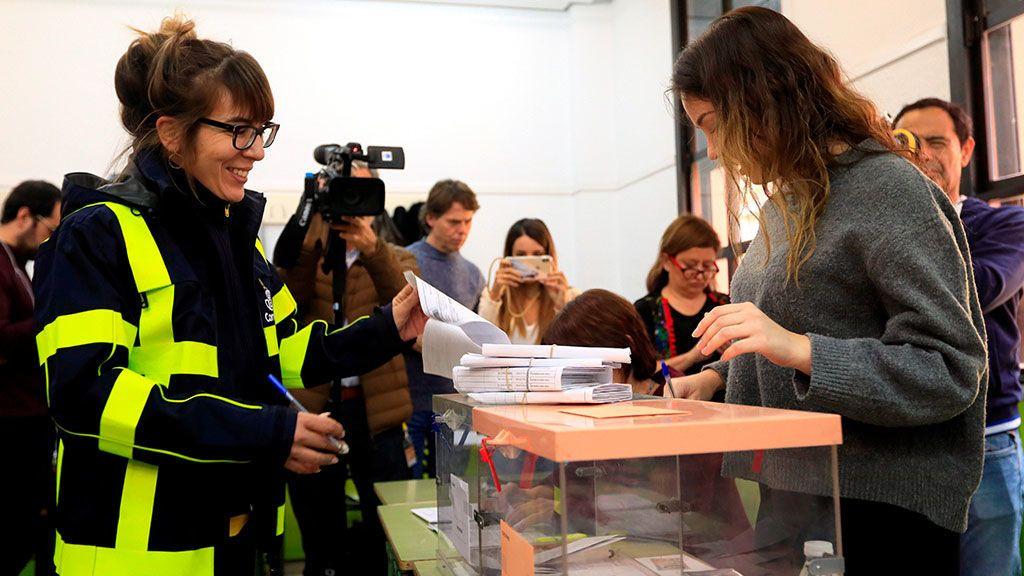 Una funcionaria de correos entrega a la presidenta de una mesa electoral un paquete de votos enviados por correo