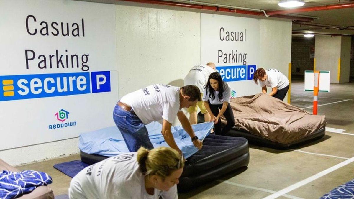 Una organización pone camas en un aparcamiento para que las personas sin hogar puedan descansar en ellas