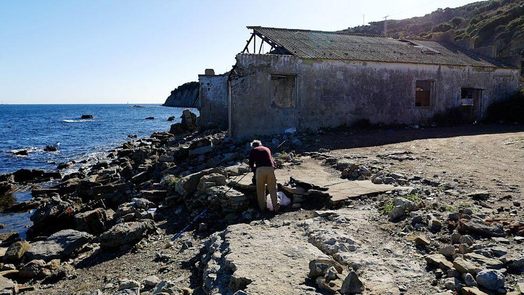 Un pescador prepara su caña en las ruinas de la ballenera