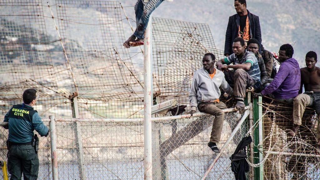 Migrantes encaramados en la valla Melilla