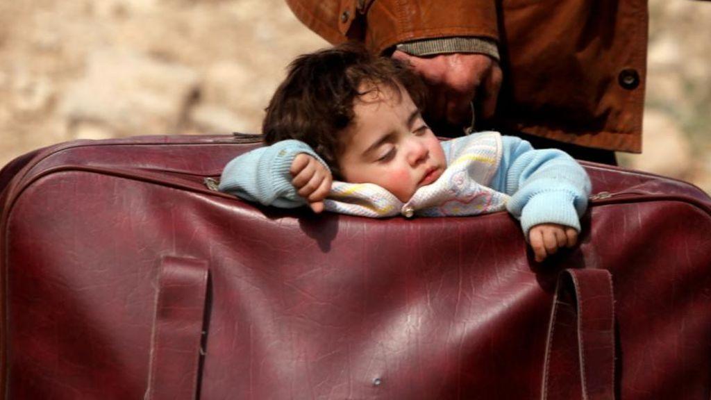 Un hombre huye de Siria llevando a su hijo en una maleta