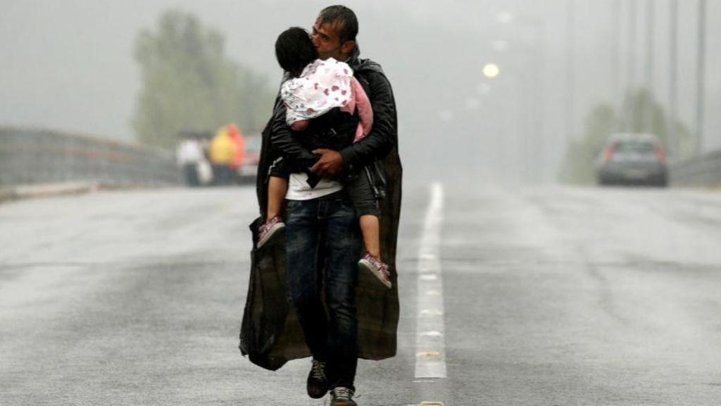 Un refugiado abraza a su hija bajo la lluvia