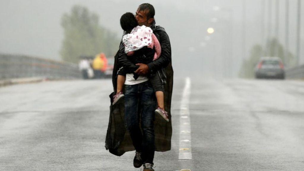 Un refugiado con su hija en brazos en la frontera de Macedonia