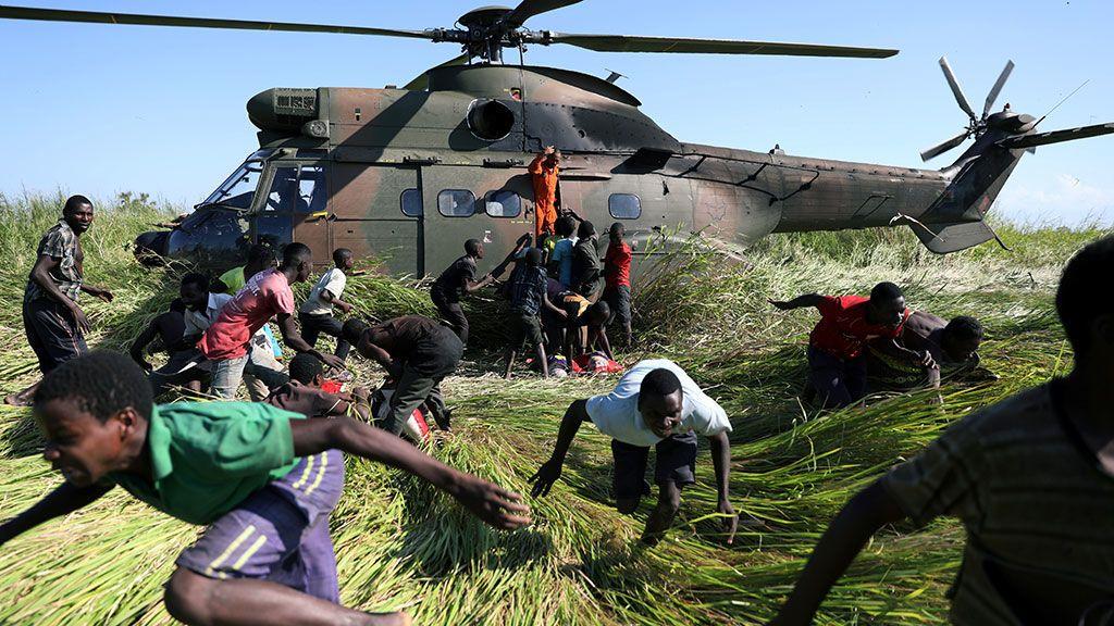 Gente corriendo después de recoger ayuda alimentaria de un helicóptero de la Fuerza de Defensa Nacional de Sudáfrica después del ciclón Idai en la aldea de Nhamatanda, cerca de Beira (Mozambique)u