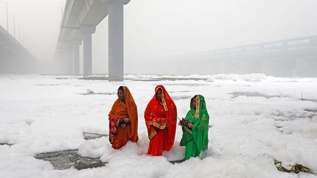 Tres mujeres adoran al dios sol en las aguas contaminadas del río Yamuna durante la fiesta religiosa hindú de Chhath Puja en Nueva Delhi (India),