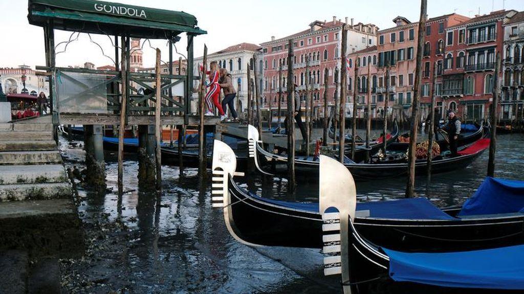 Varias góndolas en Venecia durante la marea baja