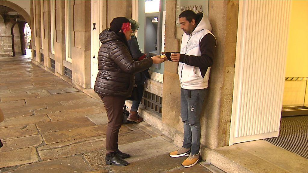 Chus, entregando chocolate y panetone a un hombre que pide en la calle