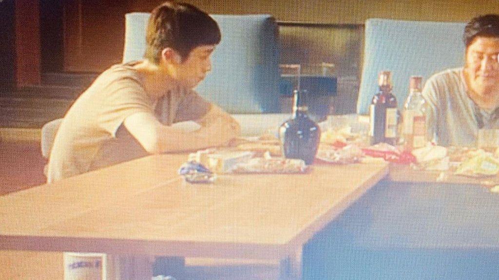La lata de patatas aparece en el suelo, bajo la mesa, en esta escena de Parásitos