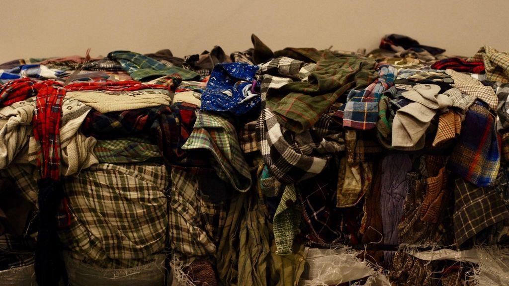 Montones de ropa reciclada en la exposición 'Fast Fashion'.