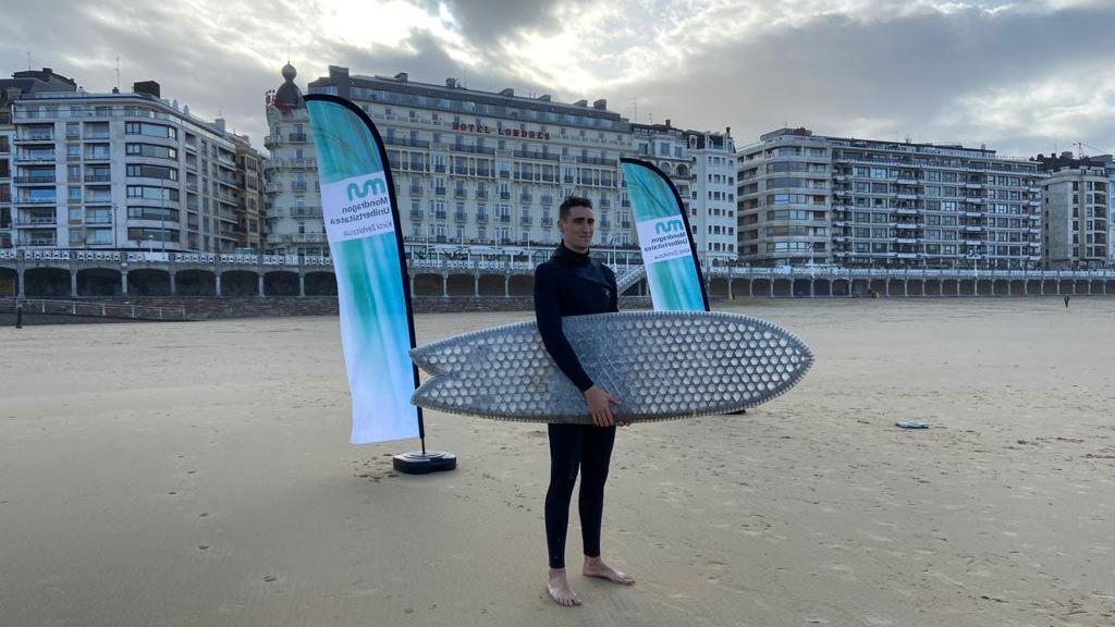 Un alumno antes de entrar en el mar para probar la tabla de surf de núcleo de cartón