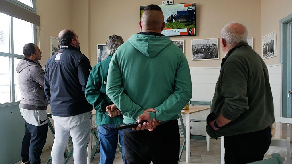 Un grupo de pescadores sigue las noticias en el puerto de Tarifa
