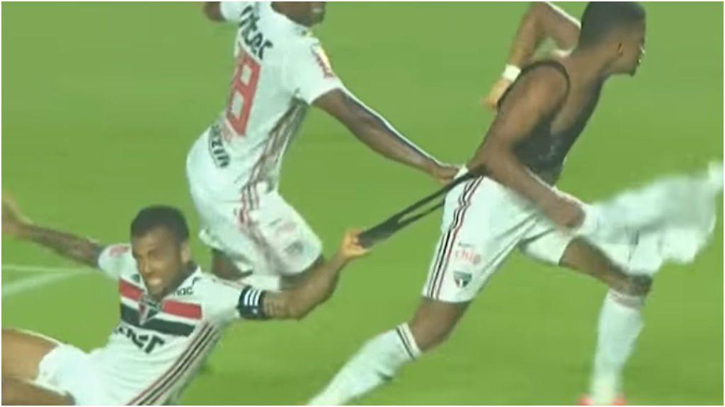 Dani Alves inventa la celebración de moda en Brasil: sujetarse al top de tu compañero mientras te arrastra por el campo