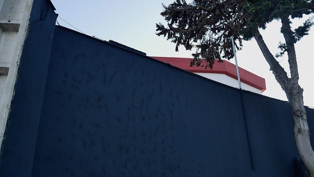 El muro que separa el colegio del club de alterne