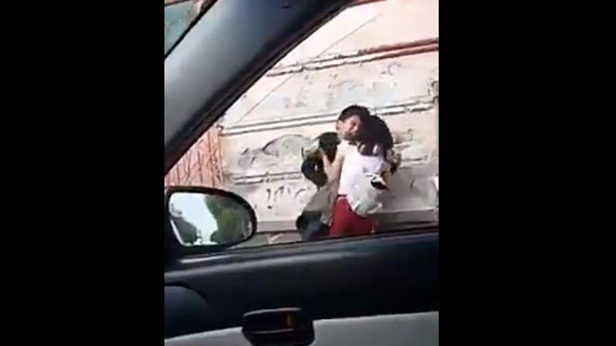 Graban a una mujer dando una paliza a su novio en plena calle: lo abofetea y muerde hasta que consigue huir