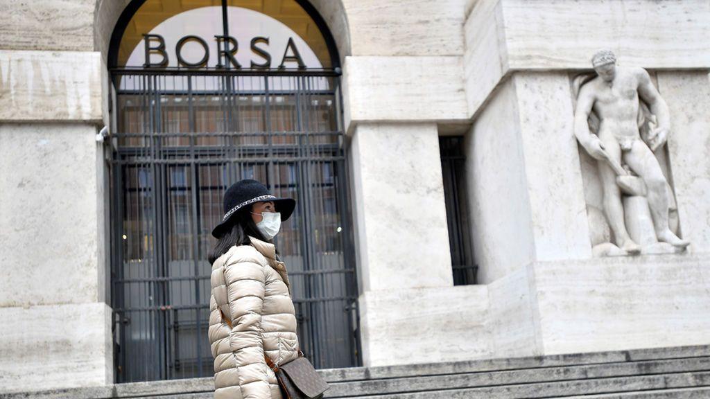 Una-turista-con-mascarilla-frente-a-la-sede-de-la-Bolsa-de-Milán,-Italia