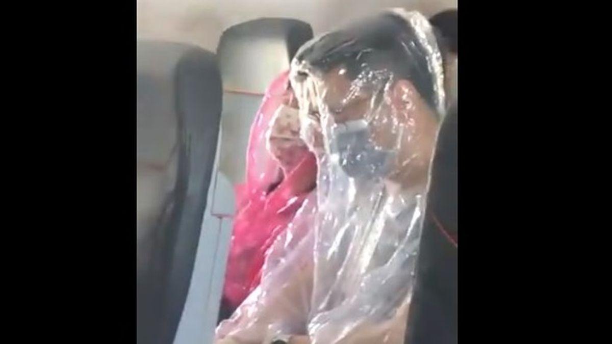 Una pareja viaja en avión envuelta en plástico ante el pánico de contagiarse por coronavirus
