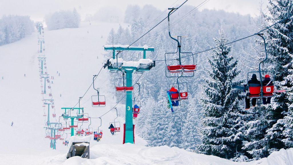 Varios esquiadores y niños en un telesilla