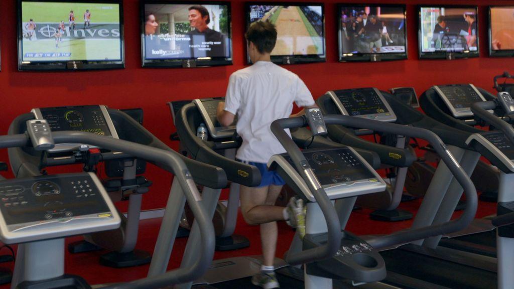Un joven corre en un gimnasio.