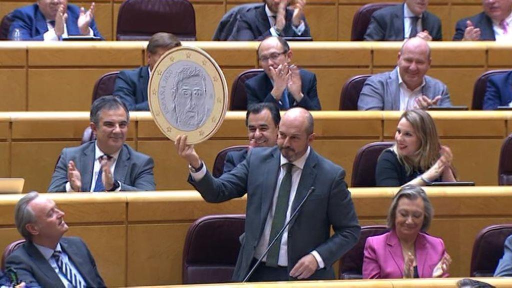 Un senador del PP enseña una moneda con la cara de Junqueras